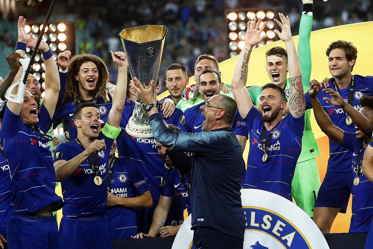 Chelsea's manager Maurizio Sarri lifts the Europa League trophy, his first major silverware as a coach, along with his jubilant team after they beat Arsenal in the final in Baku. Chelsea won 4-1 but the Italian's immediate future remains clouded by u