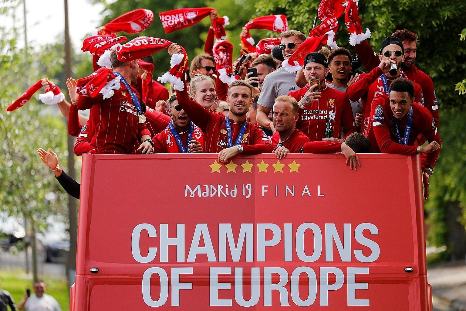 Reds captain Jordan Henderson (front, centre), Trent Alexander-Arnold (front, right) and teammates greet thousands of fans during the bus-top victory parade around Liverpool yesterday.