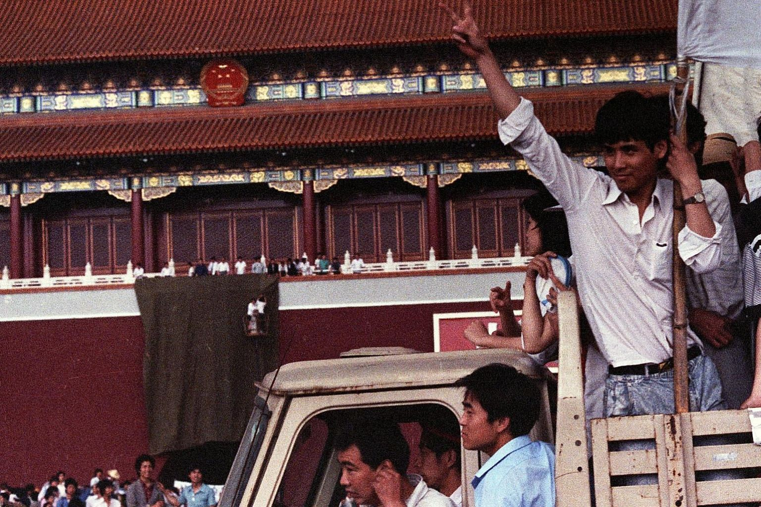 Left: A demonstrator flashing the victory sign as workmen used a drape to cover a huge portrait of chairman Mao Zedong at Tiananmen Square in 1989. Above: An armoured personnel carrier crushing one of the tents set up at Tiananmen Square by pro-democ
