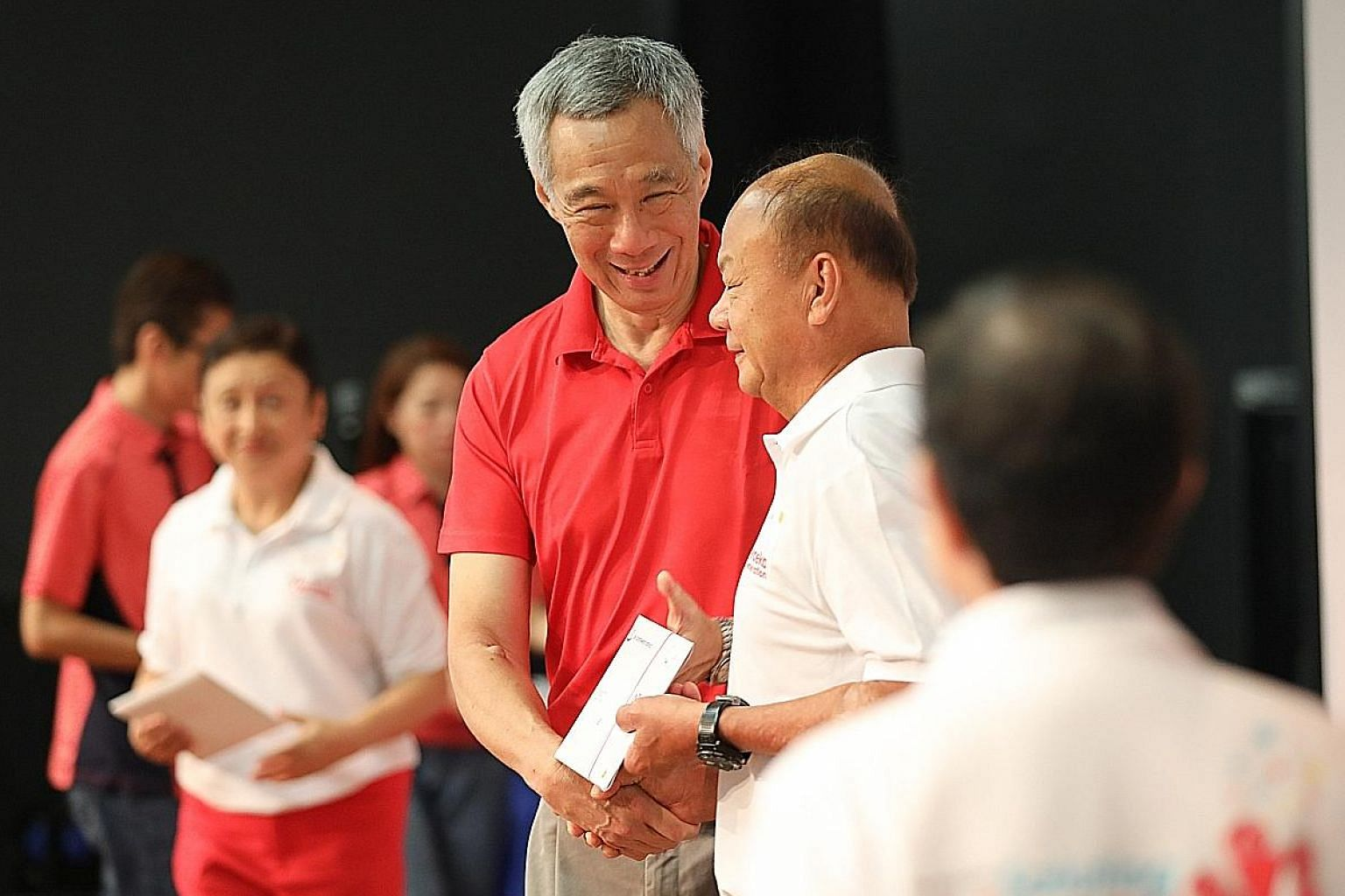 Prime Minister Lee Hsien Loong presenting welcome folders to members of the Merdeka Generation at an appreciation ceremony at the Institute of Technical Education College Central yesterday. ST PHOTO: ONG WEE JIN