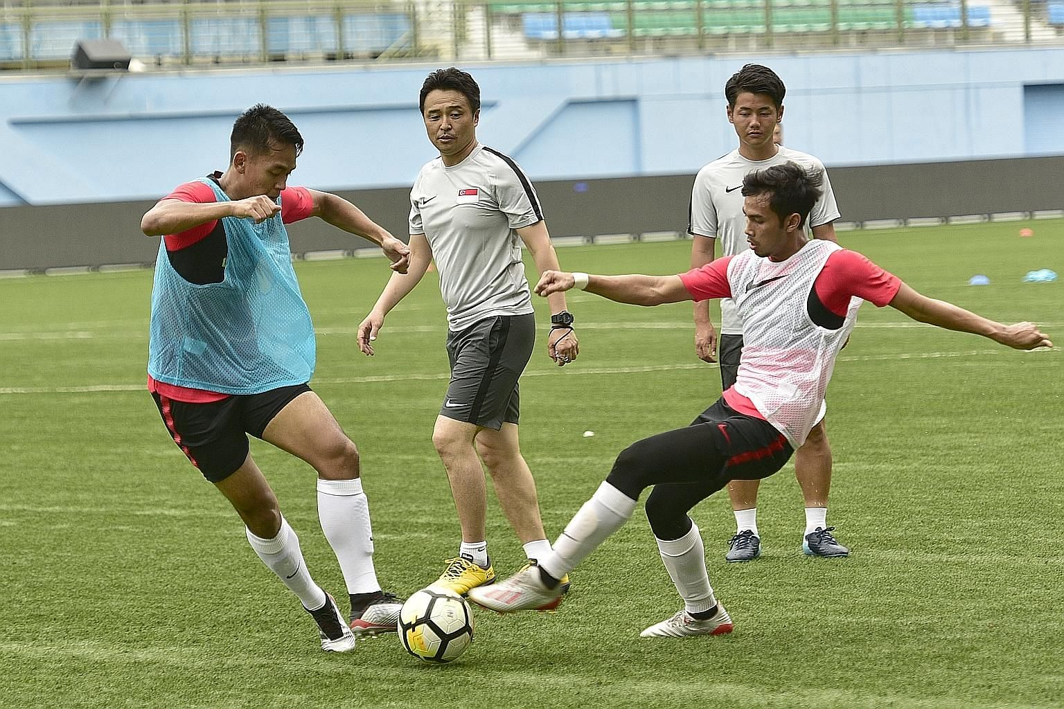 New national football coach Tatsuma Yoshida (centre) closely watching the Lions players during his first training session at the Jalan Besar Stadium yesterday.