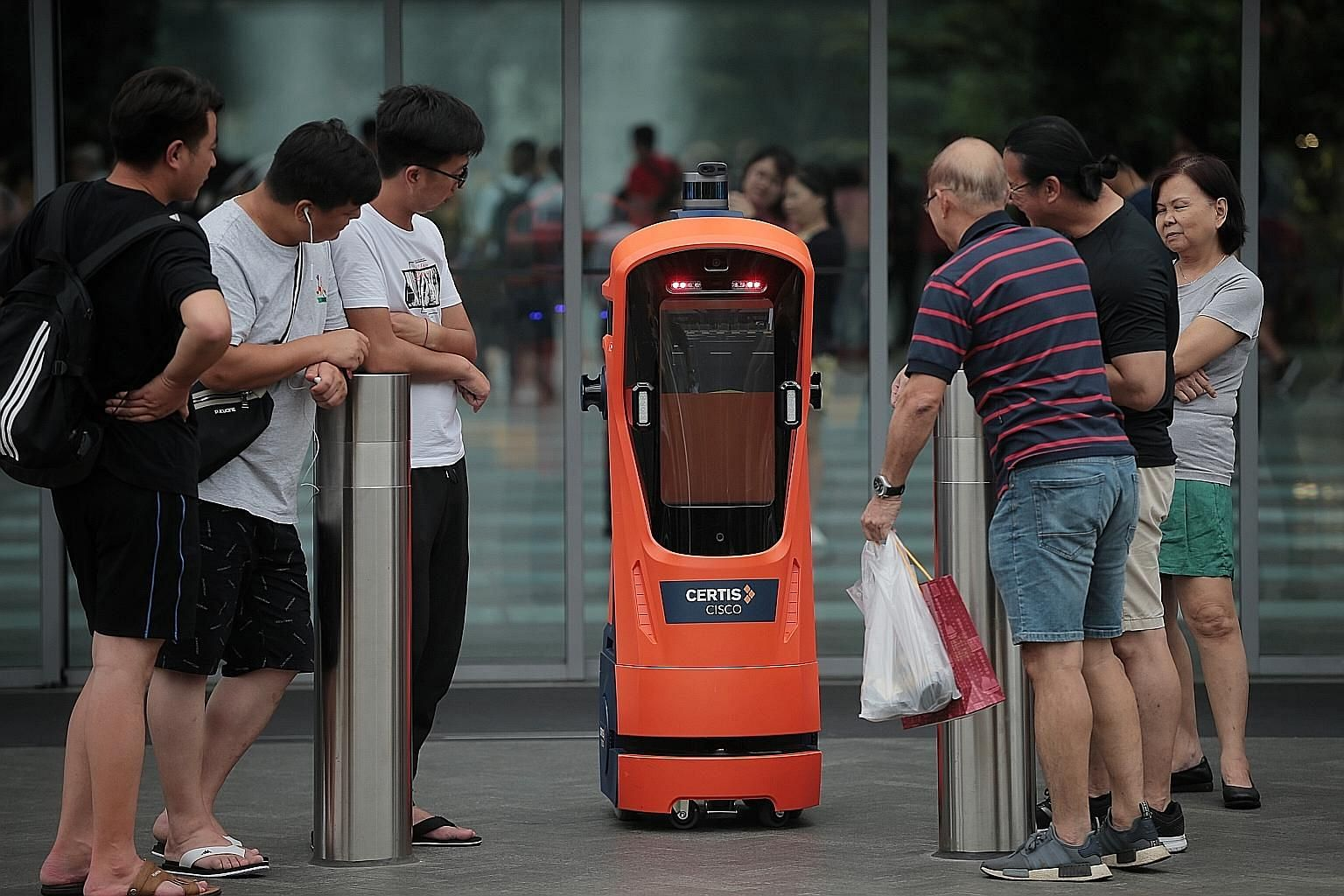 A Certis robot attracting the attention of curious visitors at Jewel Changi Airport yesterday. The robot traffic cop, which is on trial, conducts patrols but does not issue summonses.