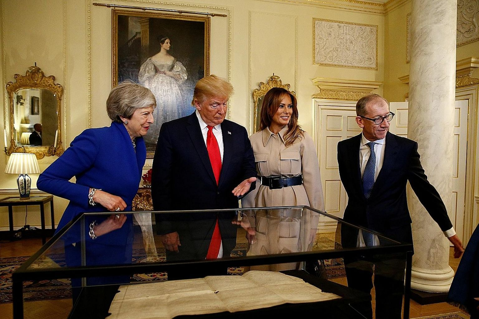 Demonstrators protesting against the visit of President Trump marching along the street in Whitehall in Central London yesterday, on the second day of his three-day state visit to Britain. PHOTO: AGENCE FRANCE-PRESSE Britain's Queen Elizabeth II, fla