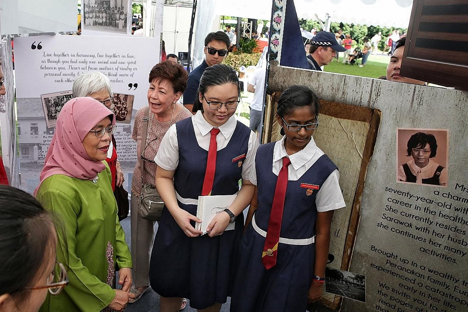 Above: President Halimah Yacob visiting the booth of the Paya Lebar Methodist Girls' School (Secondary) at the Istana open house yesterday. It was among several booths set up in conjunction with Singapore's bicentenary and showcased stories of how ed