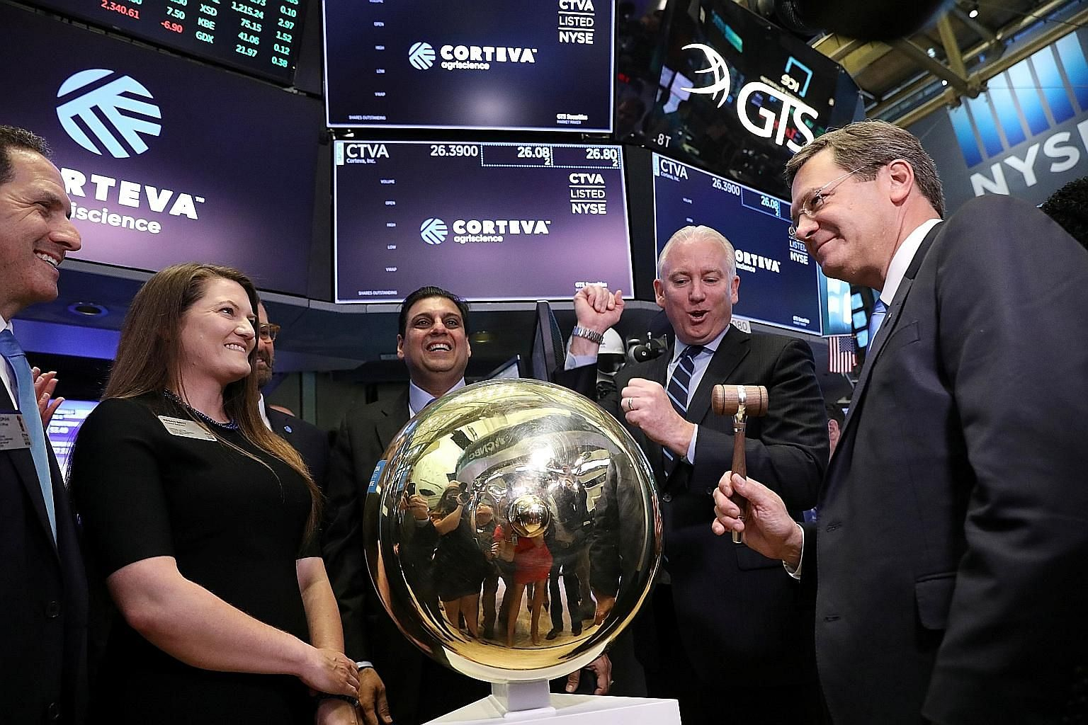 Corteva Agriscience chief executive Jim Collins (right) ringing a ceremonial bell to begin trading on the floor of the New York Stock Exchange on Monday. PHOTO: REUTERS