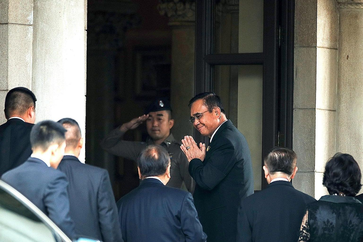 Thai Premier Prayut Chan-o-cha greeting officials at Government House yesterday in Bangkok. Mr Prayut's appointment as premier in Wednesday's joint sitting of Parliament was met with dissent by some coalition members, with one abstaining from the vot