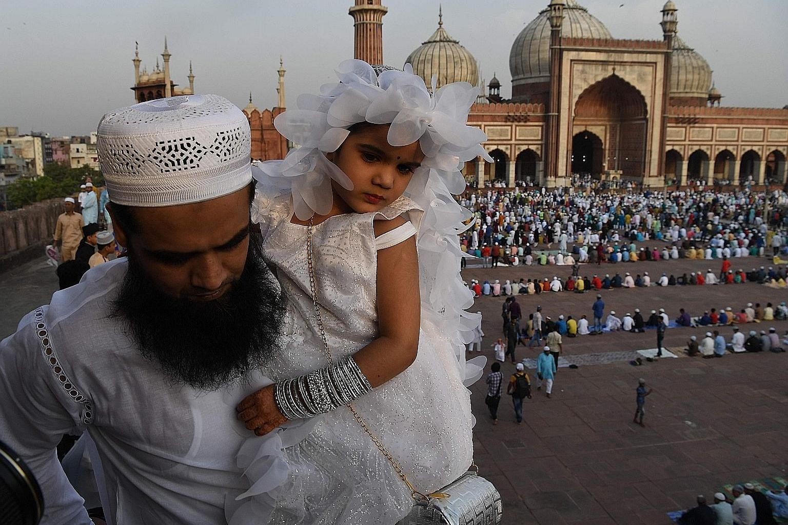 An Indian Muslim and his daughter at New Delhi's Jama Masjid mosque during Eid al-Fitr on Wednesday. Official data shows that India's Muslims fare worse than other religious communities in the country, and their continued marginalisation threatens to