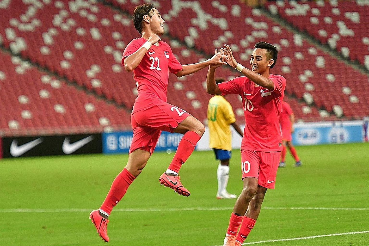 Singapore forward Gabriel Quak celebrating with Faris Ramli after he scored the Lions' third goal against the Solomon Islands in the friendly match at the National Stadium last night. Faris had scored the first goal in the fourth minute.