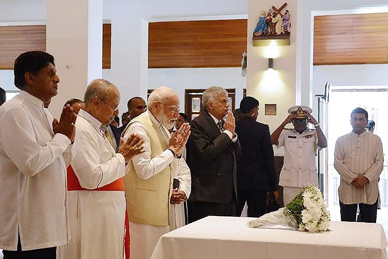 Indian Prime Minister Narendra Modi (third from left), flanked by Archbishop of Colombo Malcolm Ranjith (second from left) and Sri Lankan Prime Minister Ranil Wickremesinghe, paying respects to the victims of the Easter Sunday suicide attacks at St A