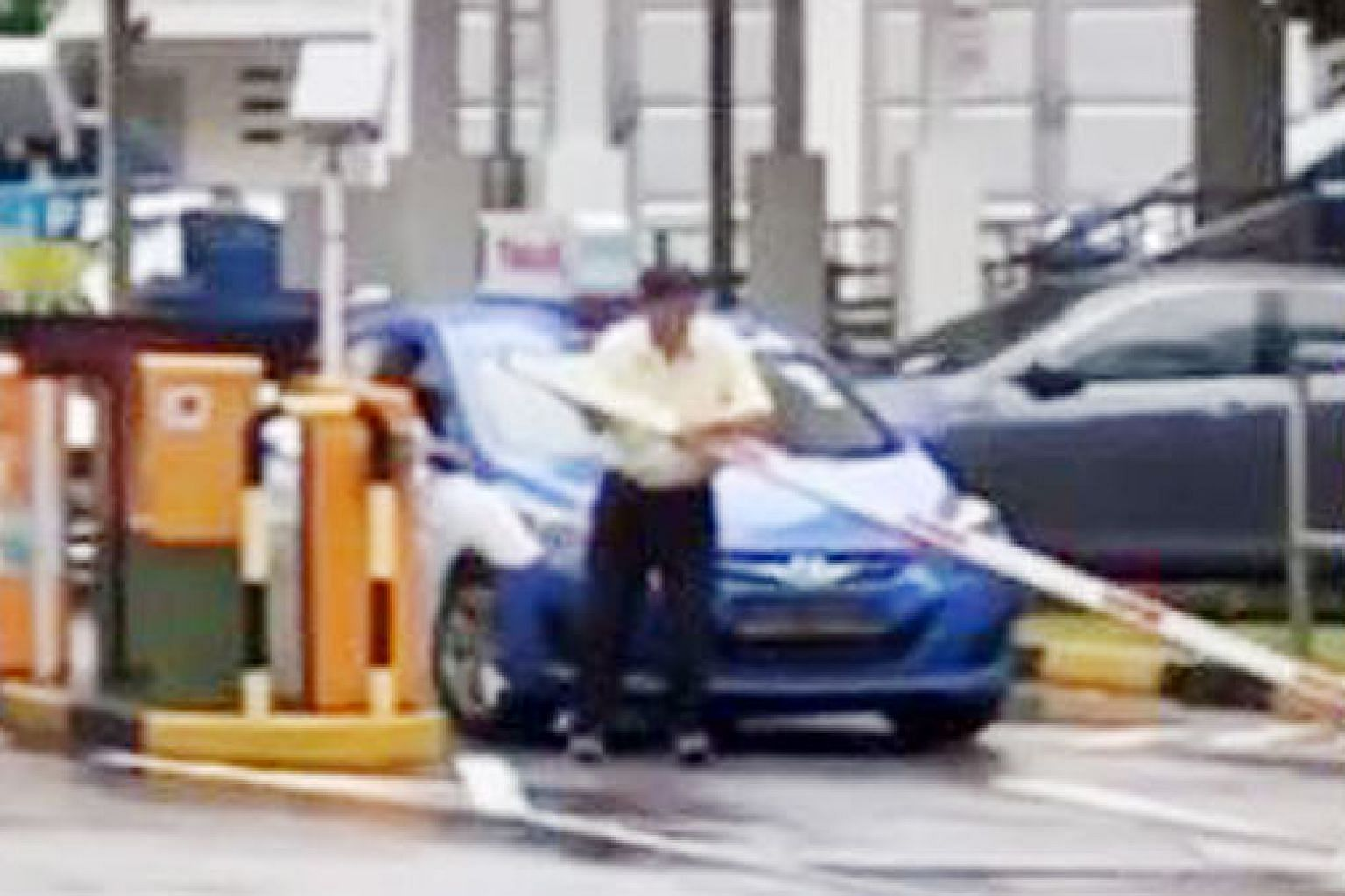 Screen grabs from the widely shared video show the taxi driver tugging at the barrier arm of the HDB carpark at Jurong East Street 32 before detaching it and throwing it on the side of the road.