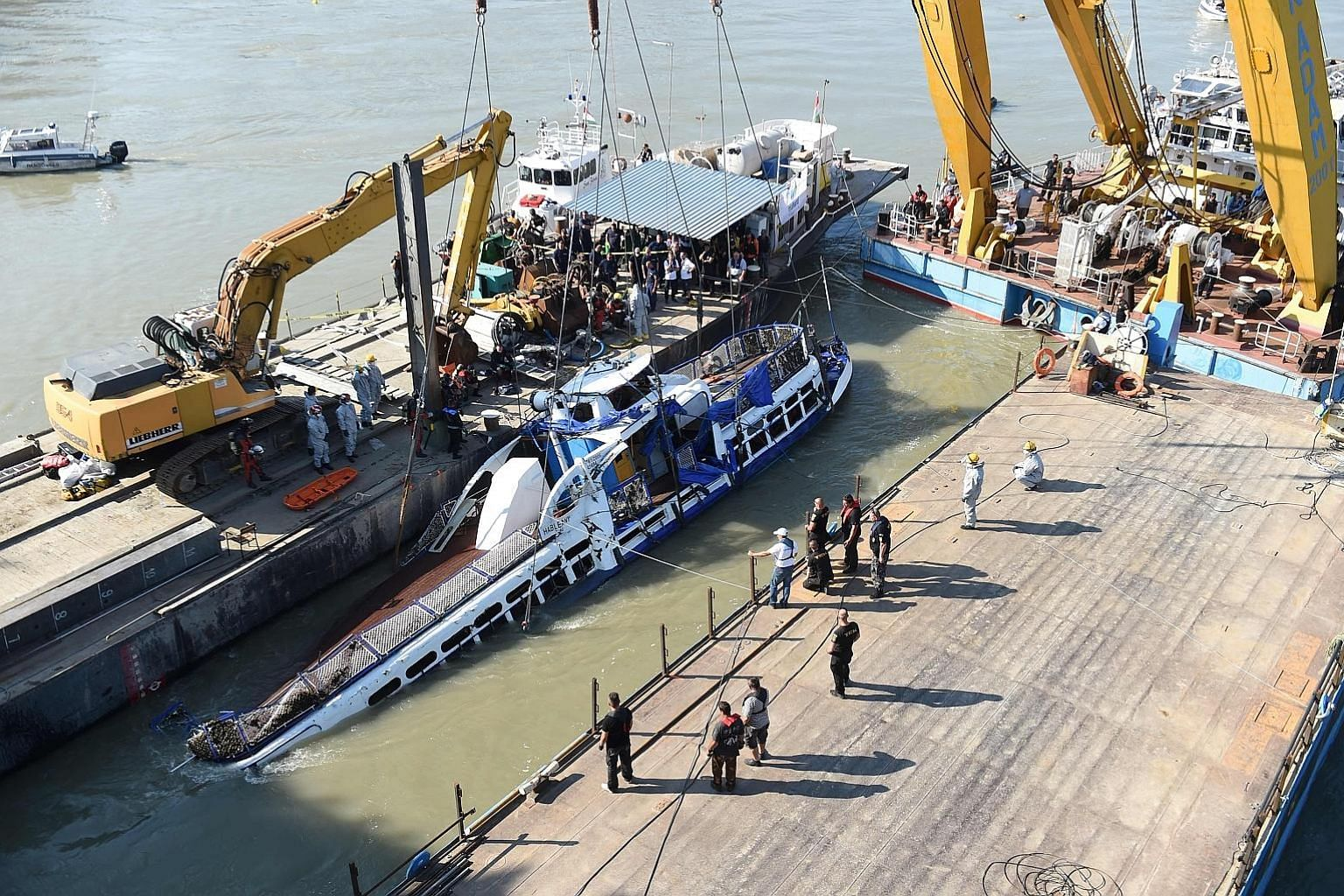 Right: Workers using a giant crane to lift the Mermaid from the Danube in Budapest yesterday. The tourist boat capsized in an accident on May 29. Above: Salvage workers saluting in respect before one of the four bodies recovered yesterday. PHOTOS: AG