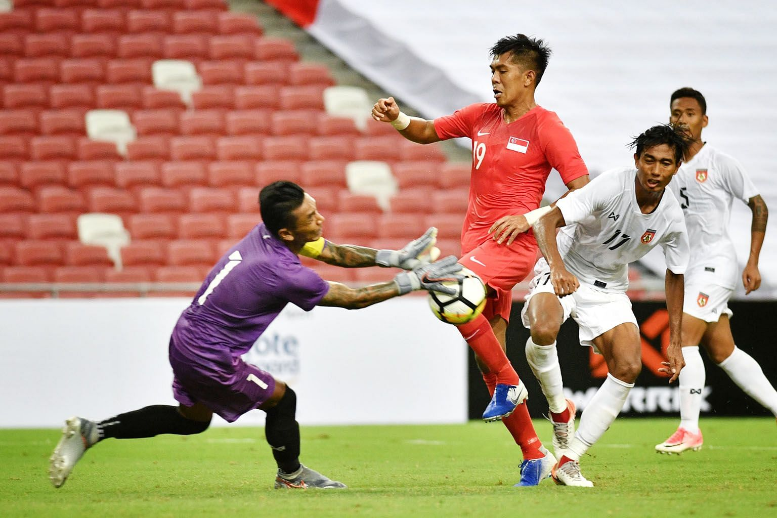 Myanmar goalkeeper Kyaw Zin Htet saving a shot from Singapore's Khairul Amri in the dying moments of their friendly match at the National Stadium last night. Kyaw Ko Ko's double sandwiched the equaliser by Gabriel Quak. ST PHOTO: CHONG JUN LIANG