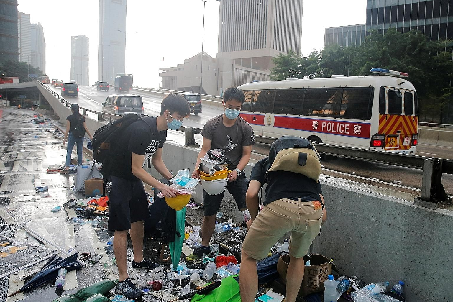 People picking out helmets, umbrellas and other items left behind by protesters in Hong Kong yesterday. Chinese state media blamed Hong Kong's opposition camp and foreign elements for inciting lawlessness. PHOTO: REUTERS