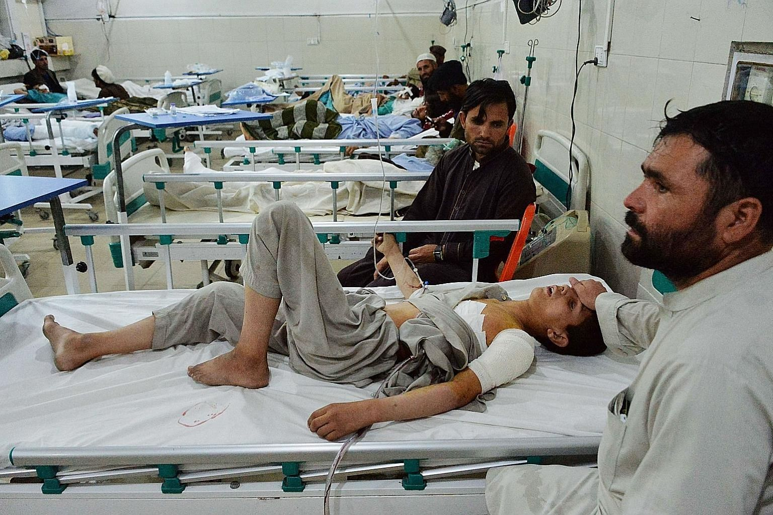 An Afghan victim receiving medical treatment in hospital after a suicide bomb attack in Jalalabad on Thursday. There was at least one child among the fatalities, while three other minors were wounded.