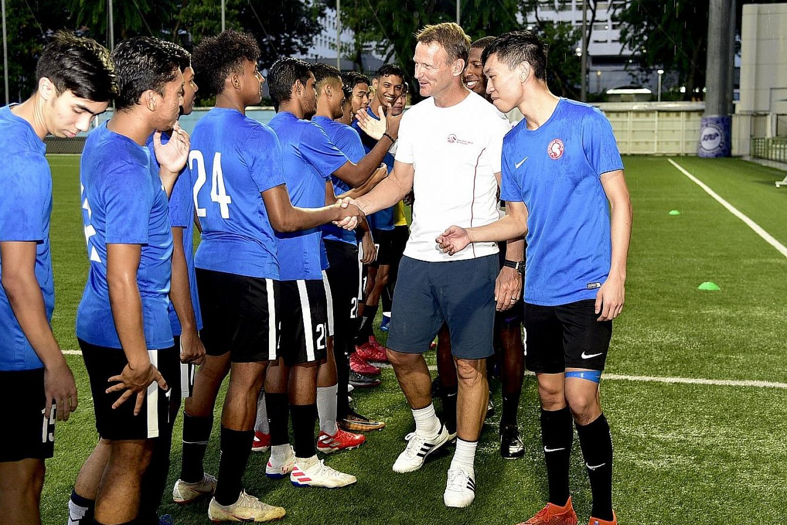 Former Tottenham and Manchester United striker Teddy Sheringham being introduced to the Young Lions by their captain Joshua Pereira at Jalan Besar Stadium on Thursday.