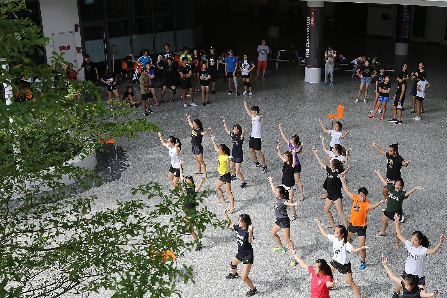 Above: NTU freshmen playing orientation games on Sentosa in 2016. Left: Students practising dance moves in 2016 for NUS' Rag and Flag day, which is part of the orientation programme.
