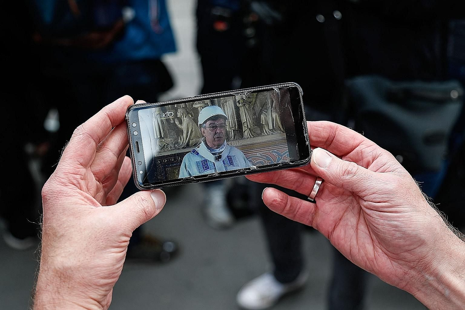 A mobile phone capturing the Archbishop of Paris Michel Aupetit, wearing a hard hat, holding mass in Notre-Dame Cathedral yesterday, the first celebration since it caught fire on April 15. PHOTO: AGENCE FRANCE-PRESSE