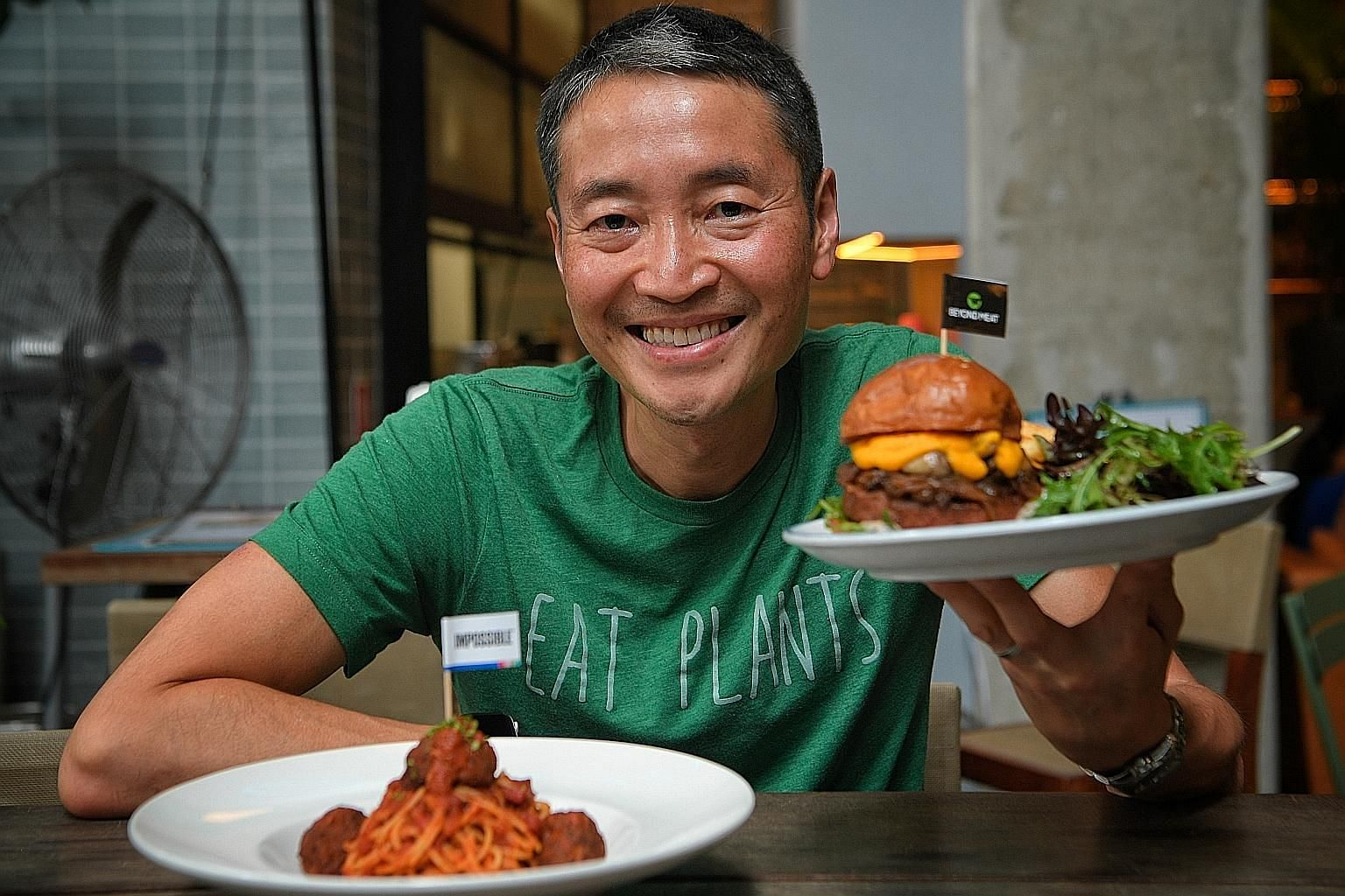 Mr Yuan Oeij, chairman of The Prive Group, with its Impossible Meatball Spaghetti and a burger with a Beyond Meat Patty. Restaurateurs must come up with innovative dishes with the meat alternatives so as to keep patrons interested, he says.