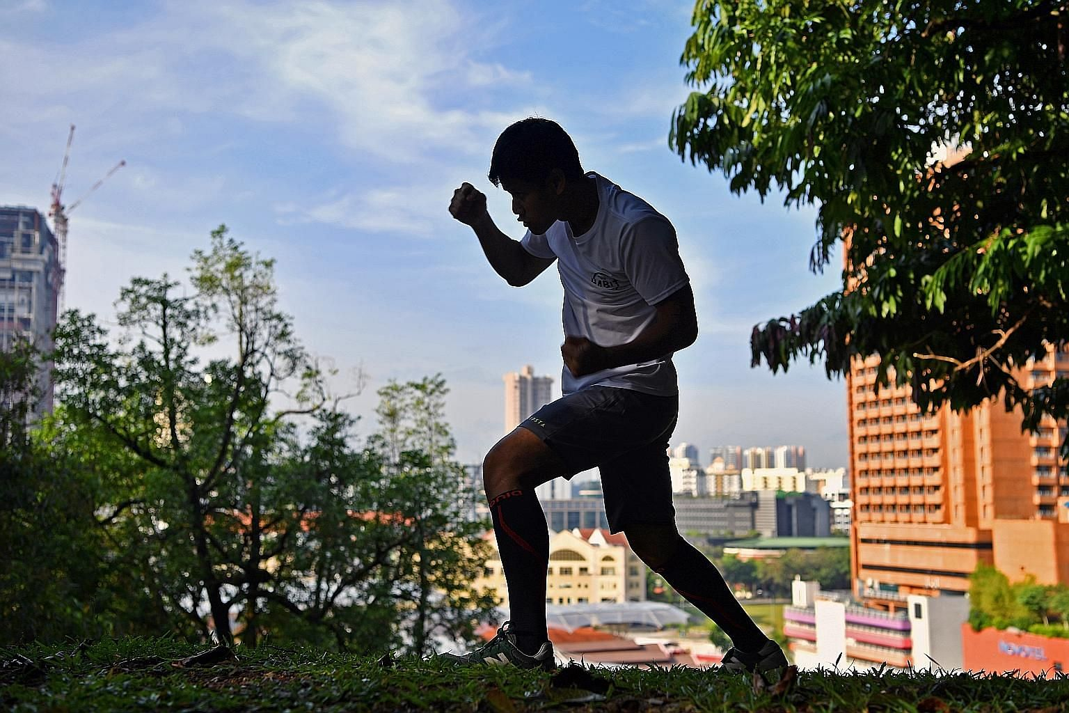 Muhamad Ridhwan shadowboxing after his morning run at Fort Canning Park. The first phase of training before a fight consists of endurance runs, sprints, strength and conditioning exercises, and shadowboxing. The boxer lives by the dictum that one needs to
