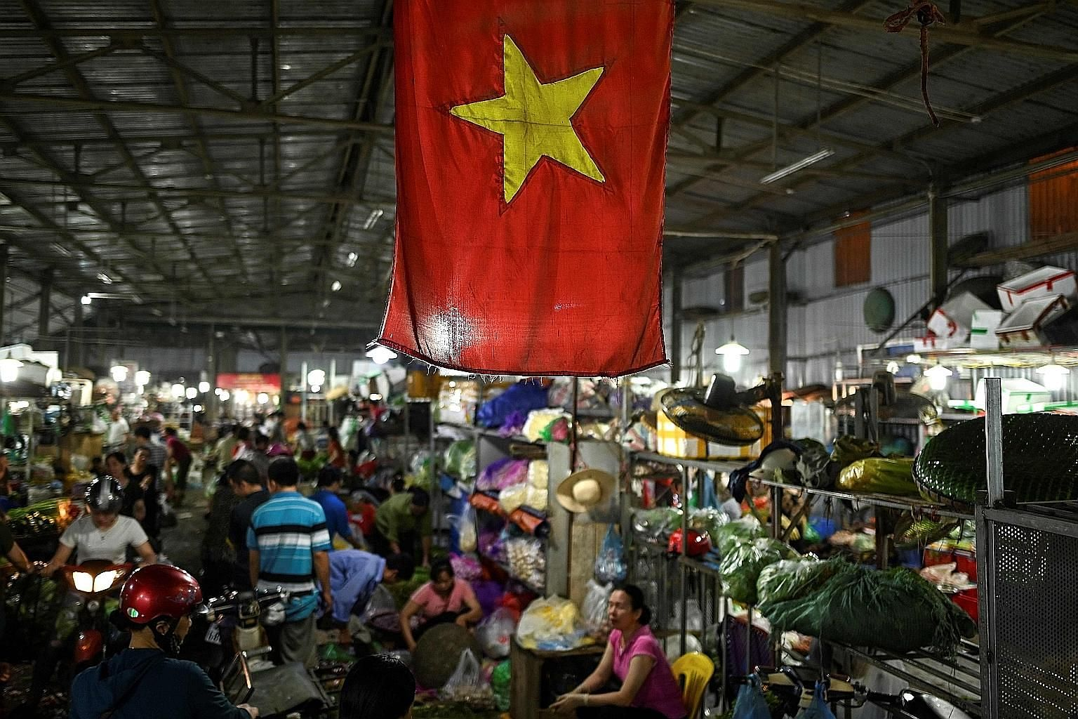 Left: Women working at a Maxport garment factory in Thai Binh, a coastal province in the north, on June 13. Workers at a shoe factory in Dong Van Town, in northern Vietnam. Proximity to China, cheap labour, a raft of trade pacts and ongoing efforts t