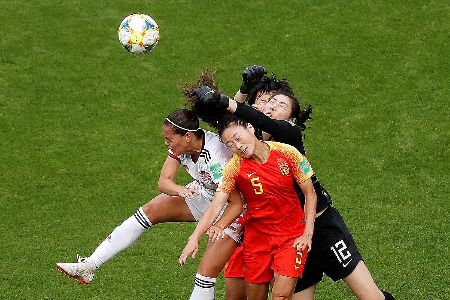China defender Wu Haiyan and goalkeeper Peng Shimeng trying to block out the threat of Spain forward Andrea Falcon during the 0-0 World Cup draw on Monday. Both teams are through to the knockout stage of the competition despite the stalemate.