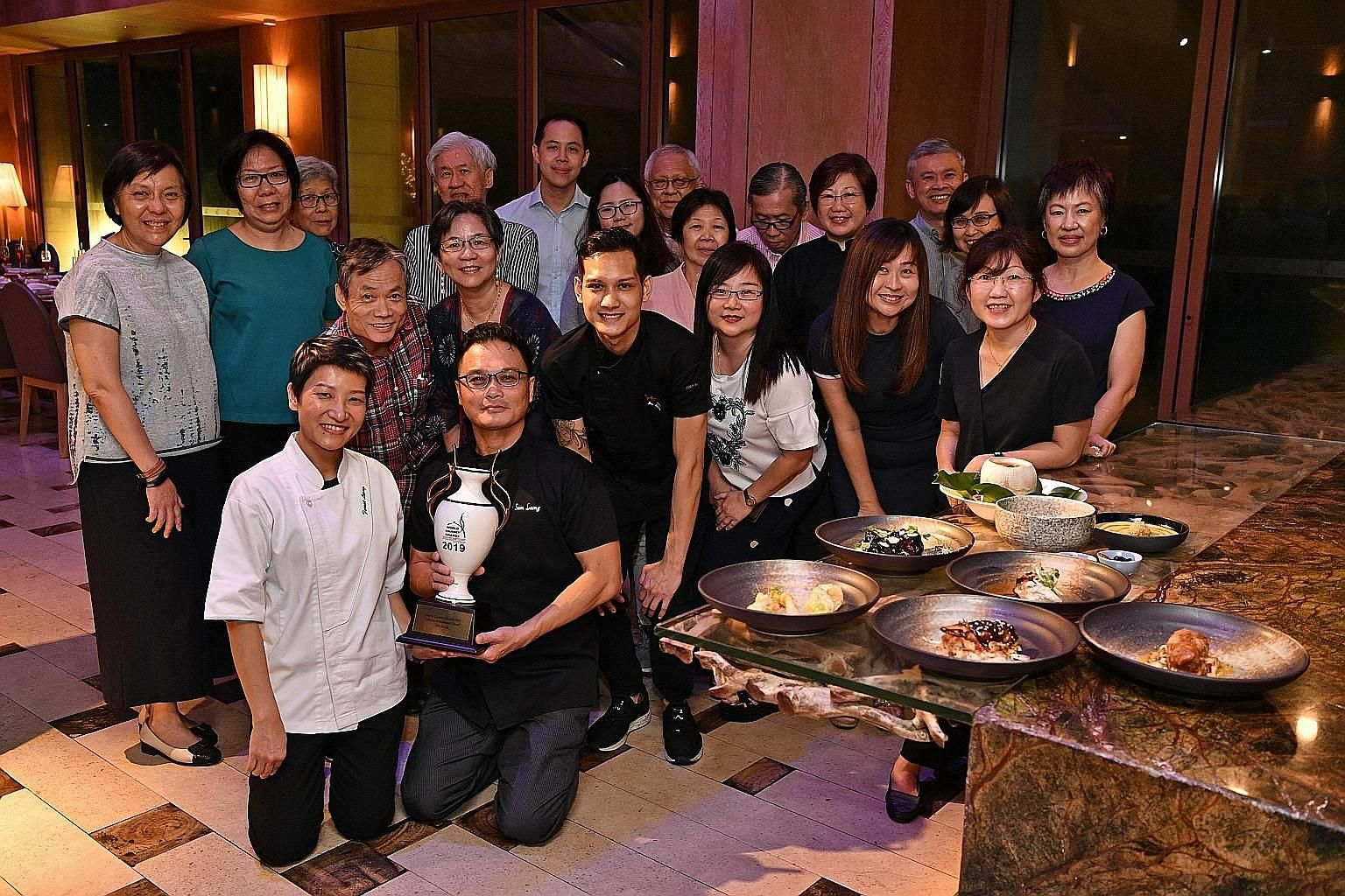 Celebrity chef Sam Leong (kneeling with his wife Forest and son Joe, on the right) with Straits Times subscribers who won a six-course dinner to his restaurant, Forest, as part of the ST+ news with benefits programme.