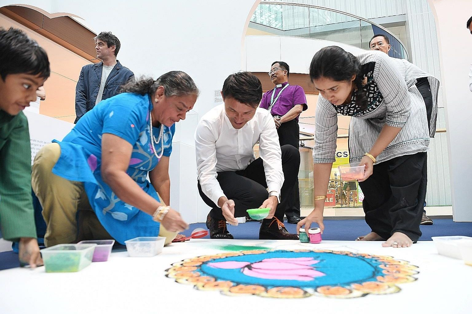 Senior Parliamentary Secretary for Culture, Community and Youth Baey Yam Keng joining Madam Vijaya Mohan, her grandson Pravan Bakshi and niece Amirta Ravikumaran in giving the finishing touches to rangoli art at the launch of the Many Beliefs, One Fu