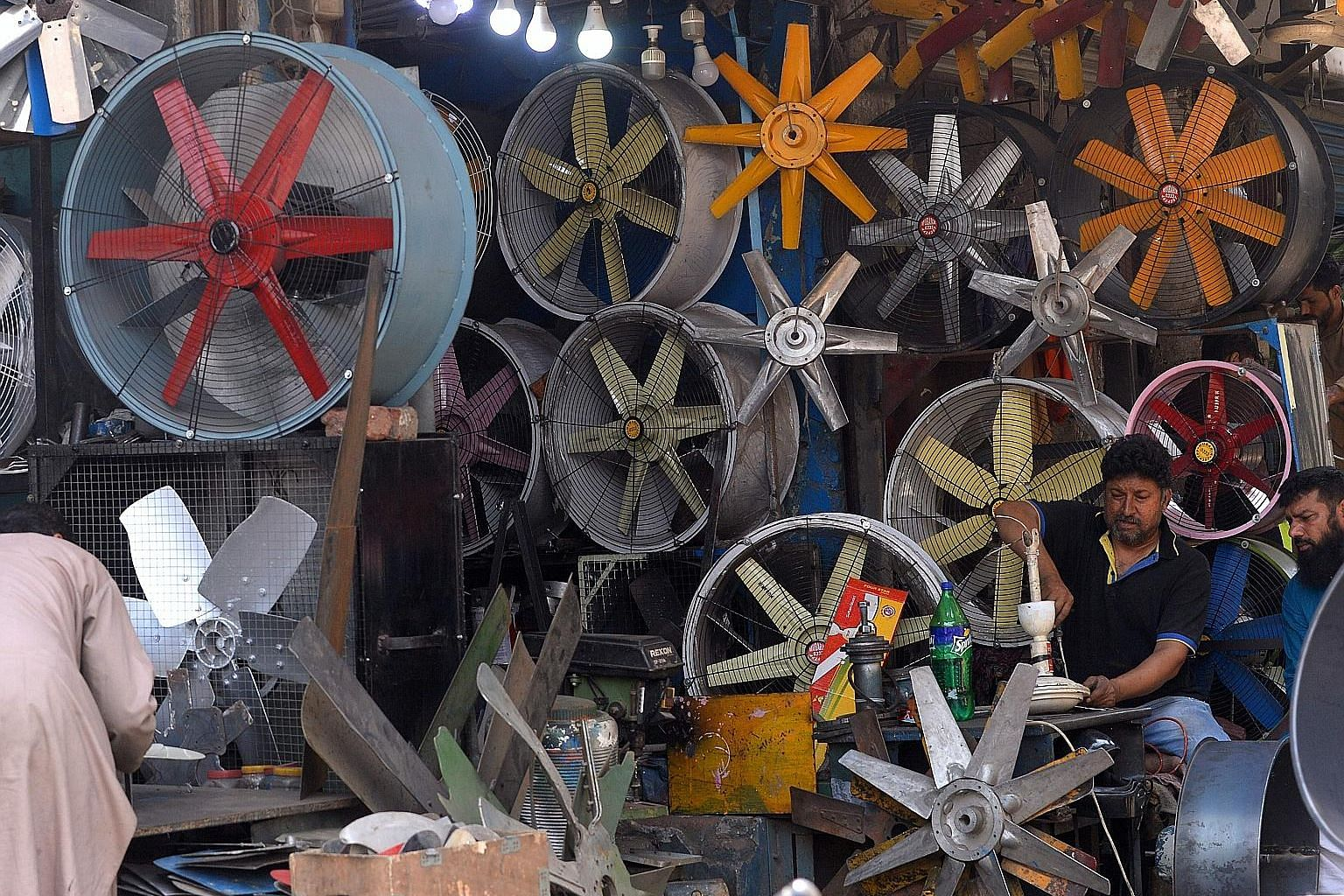 A man repairing a fan at his Lahore workshop. The 53.7 deg C (plus or minus 0.4 degree uncertainty) in Turbat, Pakistan, on May 28, 2017, is the 4th highest ever recorded. PHOTO: AGENCE FRANCE-PRESSE