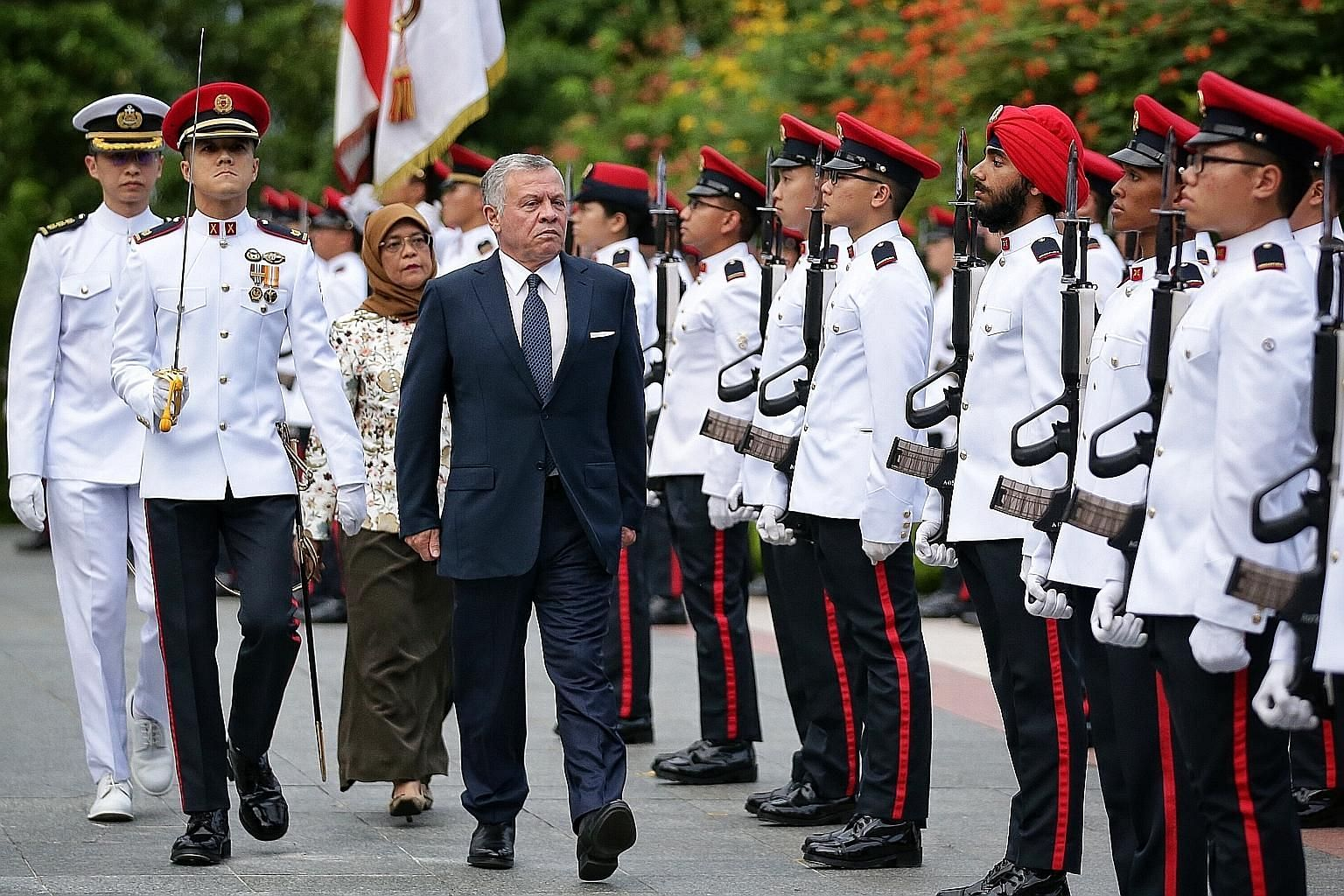 Jordan's King Abdullah II inspecting a guard of honour with President Halimah Yacob at the Istana yesterday. This is the King's third state visit to Singapore.
