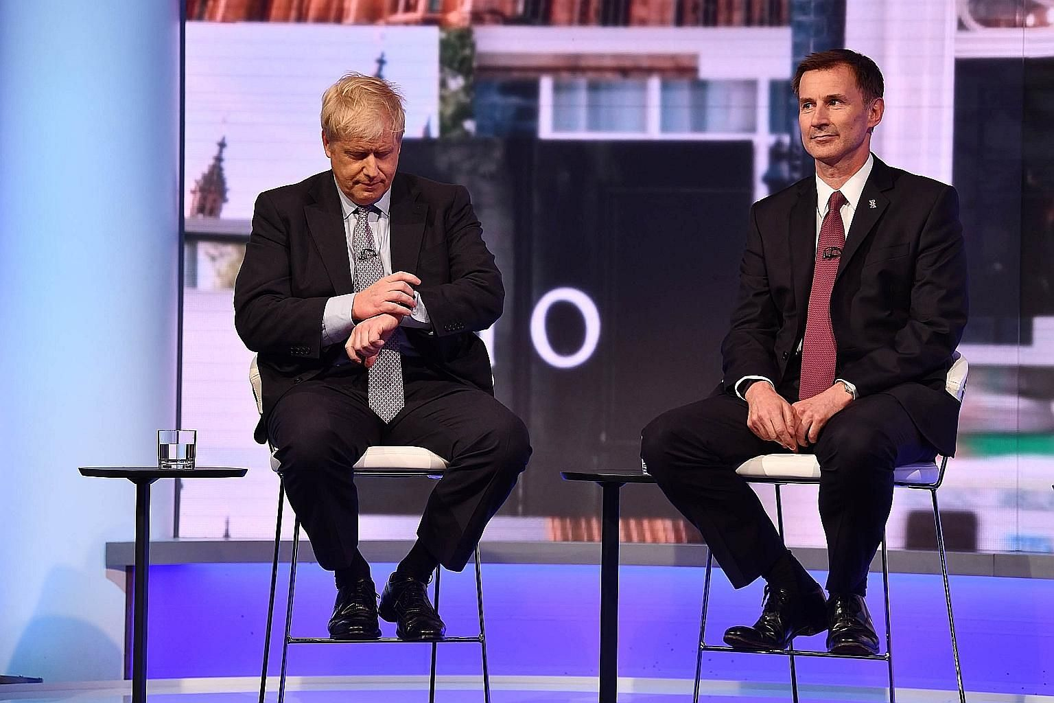 Mr Boris Johnson (left) and Mr Jeremy Hunt in a candid moment during a BBC television leadership debate in London on Tuesday. The two angling to be Britain's next leader have vowed to renegotiate the Brexit deal with the EU and get a better one befor