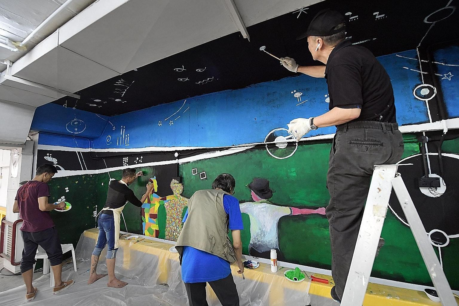Renowned sculptor Sun Yu-li (far right) and a group of former offenders giving a fresh look to Parklane Shopping Mall's carpark by painting a mural on one of its walls yesterday. Called Turning Points, the mural was designed and painted by Sun, artis