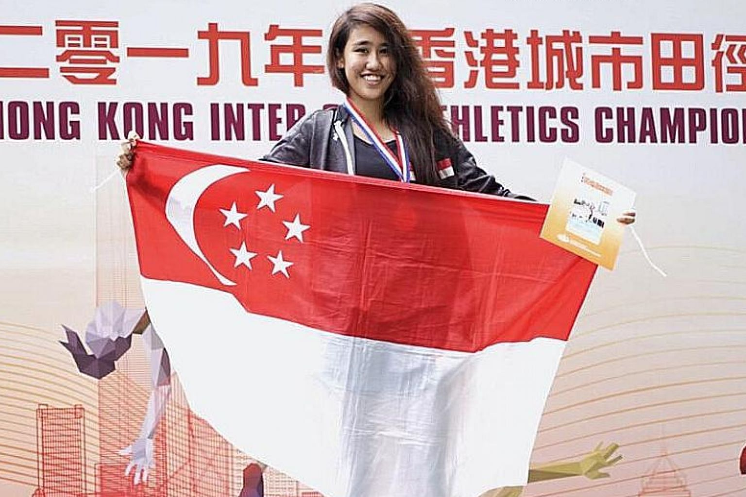 A proud Tia Louise Rozario holding the Singapore flag after she breaks the national triple jump record en route to winning the gold medal at the Hong Kong Inter-City Athletics Championships yesterday.