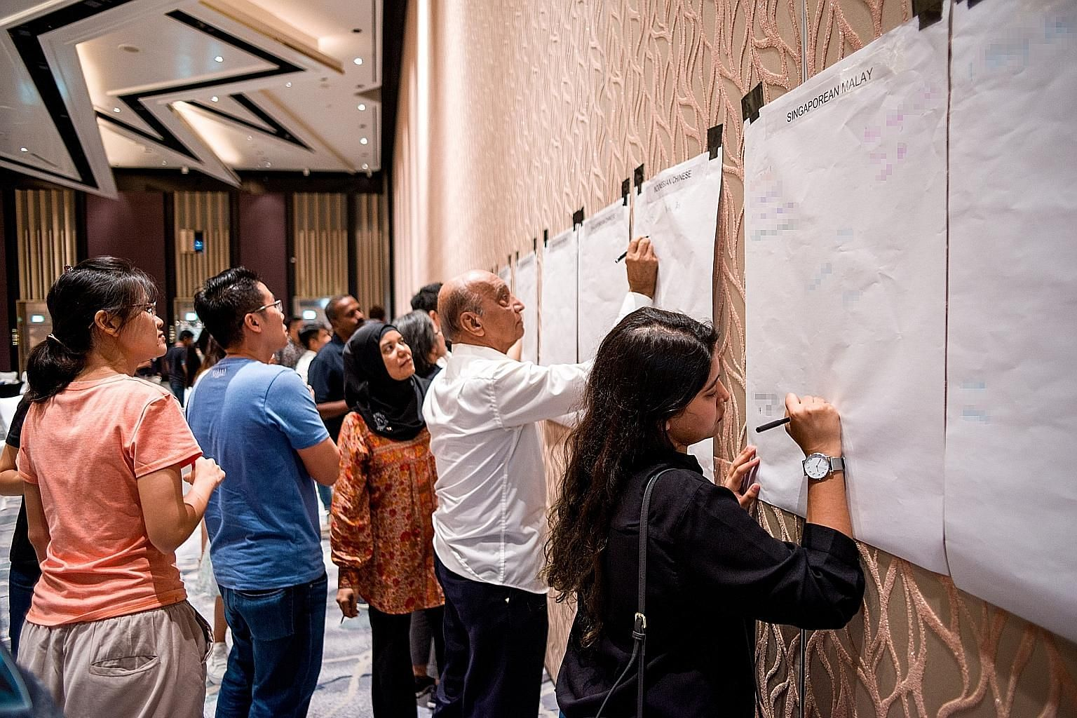 Participants at yesterday's workshop scribbling down the biased notions that they have heard about certain groups of people. PHOTO: ONEPEOPLE.SG