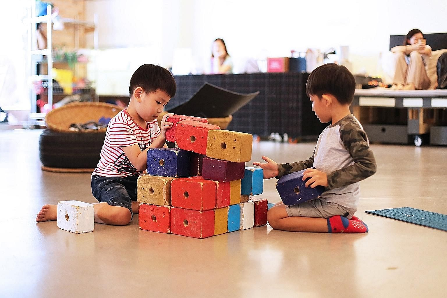 At Playeum, a children's centre for creativity, Eden Eyok (left), five, and Tan Hong Kai, six, can stack blocks or play with coloured tiles. Writer and researcher Hidayah Amin (centre, in black shirt) demonstrating sign language during an inclusive s