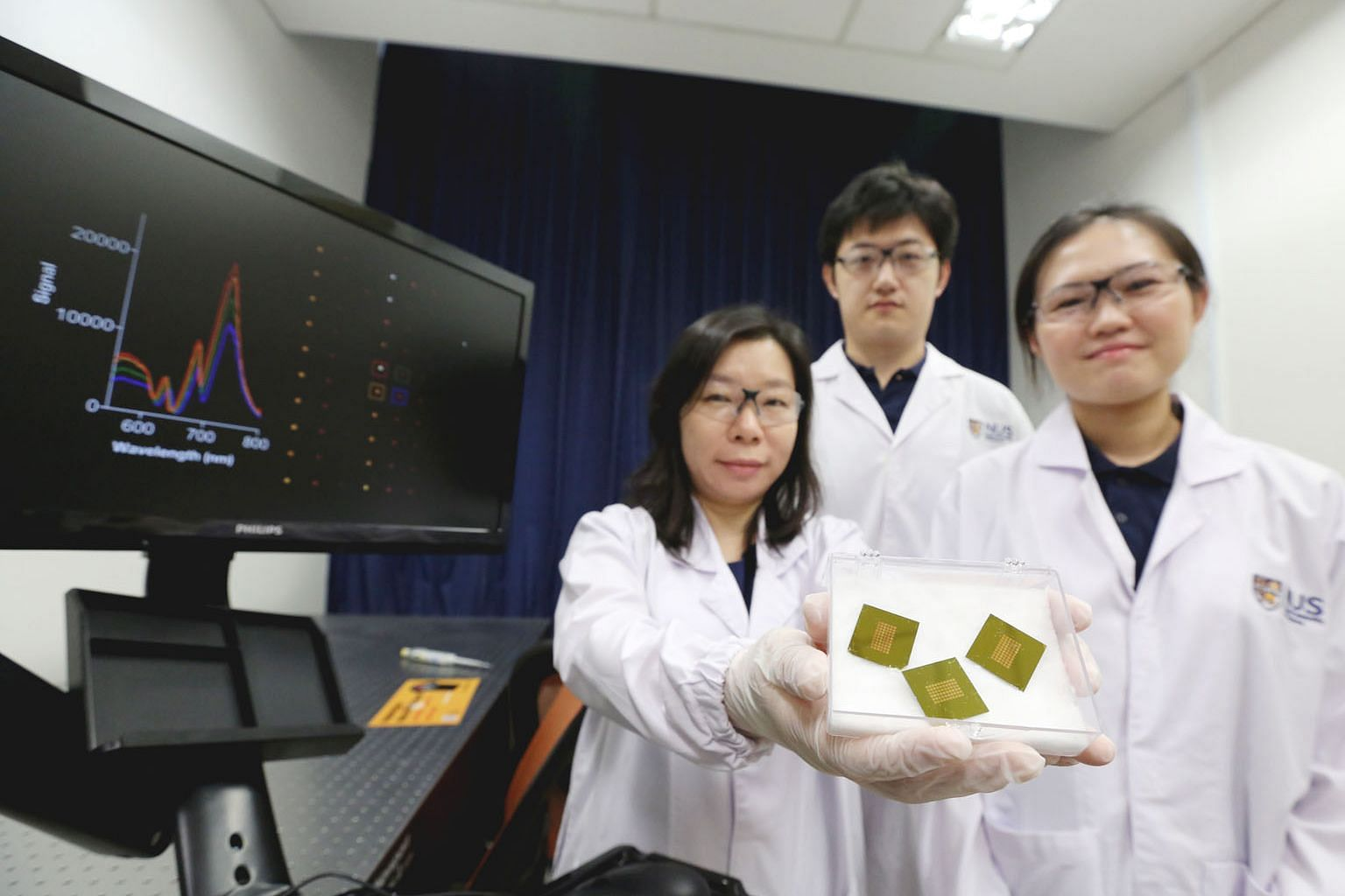 The NUS researchers (from far left) Assistant Professor Shao Huilin with doctoral students Zhang Yan and Carine Lim behind the test that can detect a molecule indicating early-stage Alzheimer's disease, the most common cause of severe dementia.
