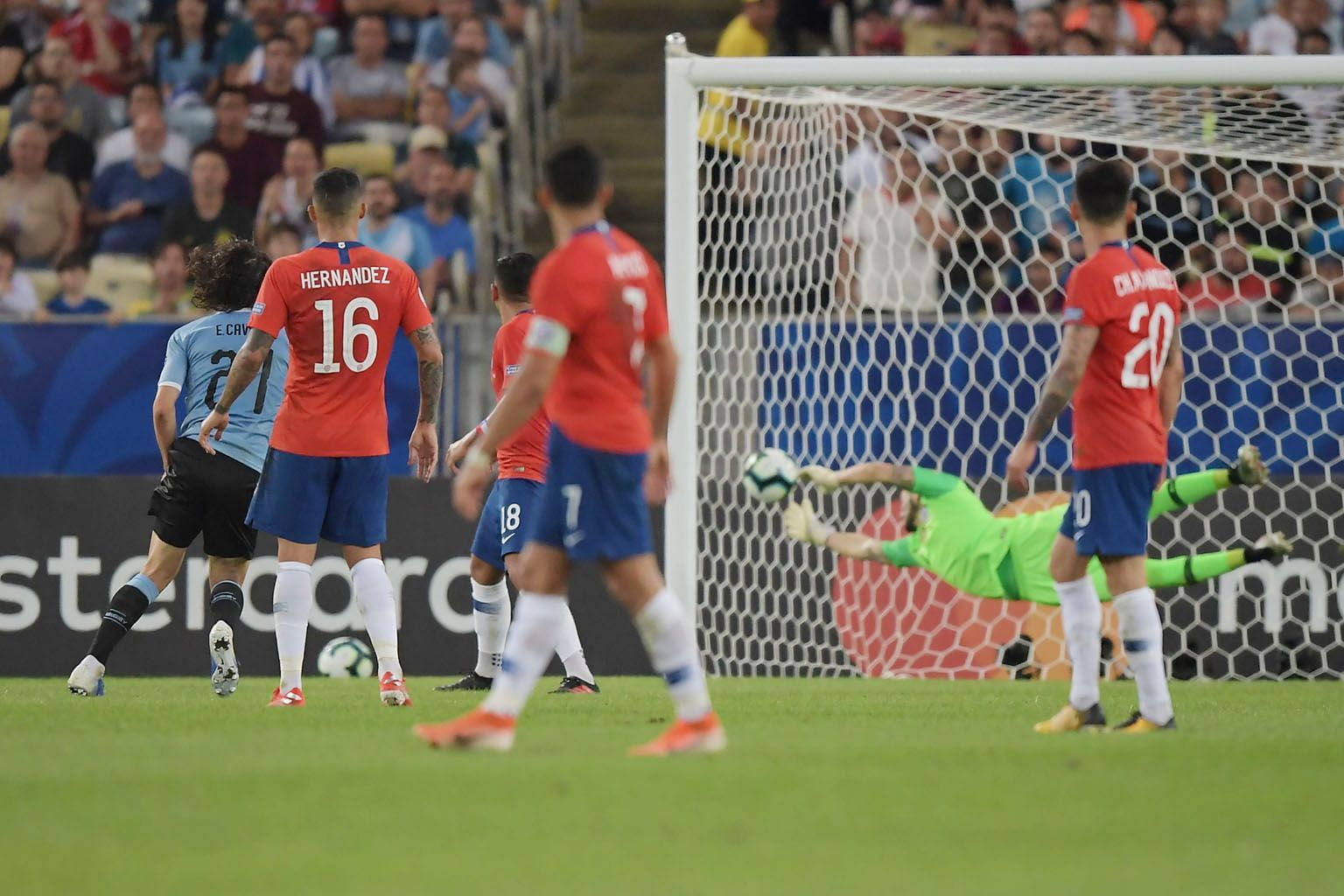 Uruguay's Edinson Cavani heading past Chile goalkeeper Gabriel Arias for the only goal of the Copa America match at Maracana Stadium in Rio de Janeiro, Brazil on Monday. Both teams made the quarter-finals. PHOTO: AGENCE FRANCE-PRESSE