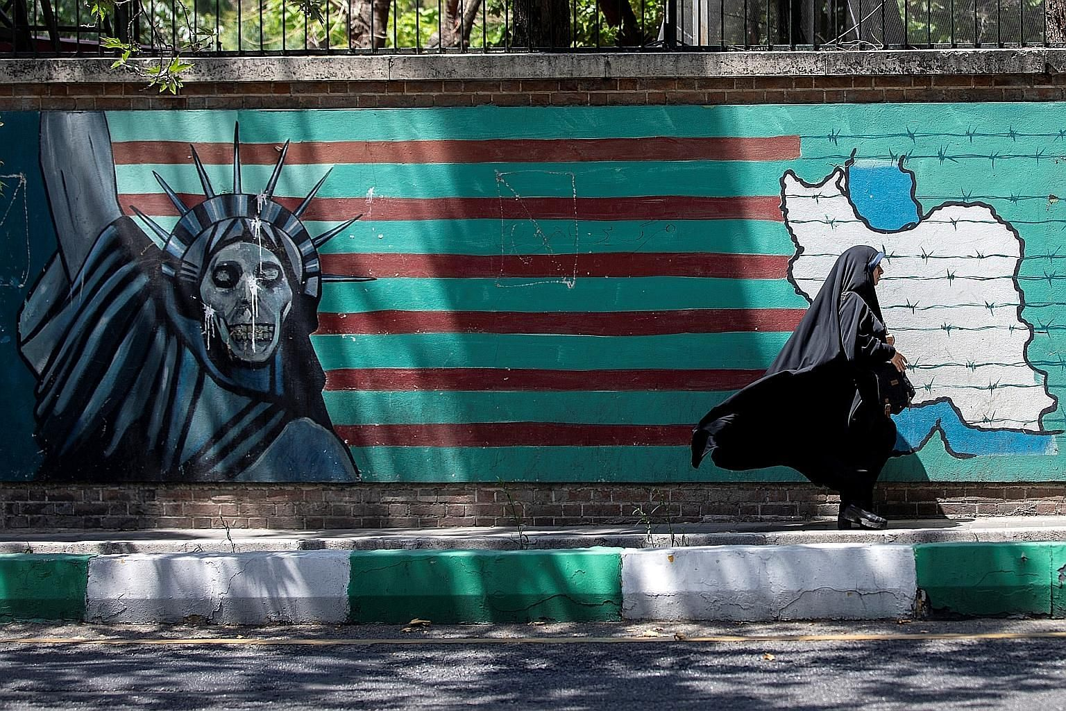 A mural showing the Statue Of Liberty painted with a skull face in Teheran. Iran has said that it would be Washington's fault if it exceeds the 300kg stockpile threshold as the 2015 nuclear deal allows Iran to sell excess uranium abroad to keep its s