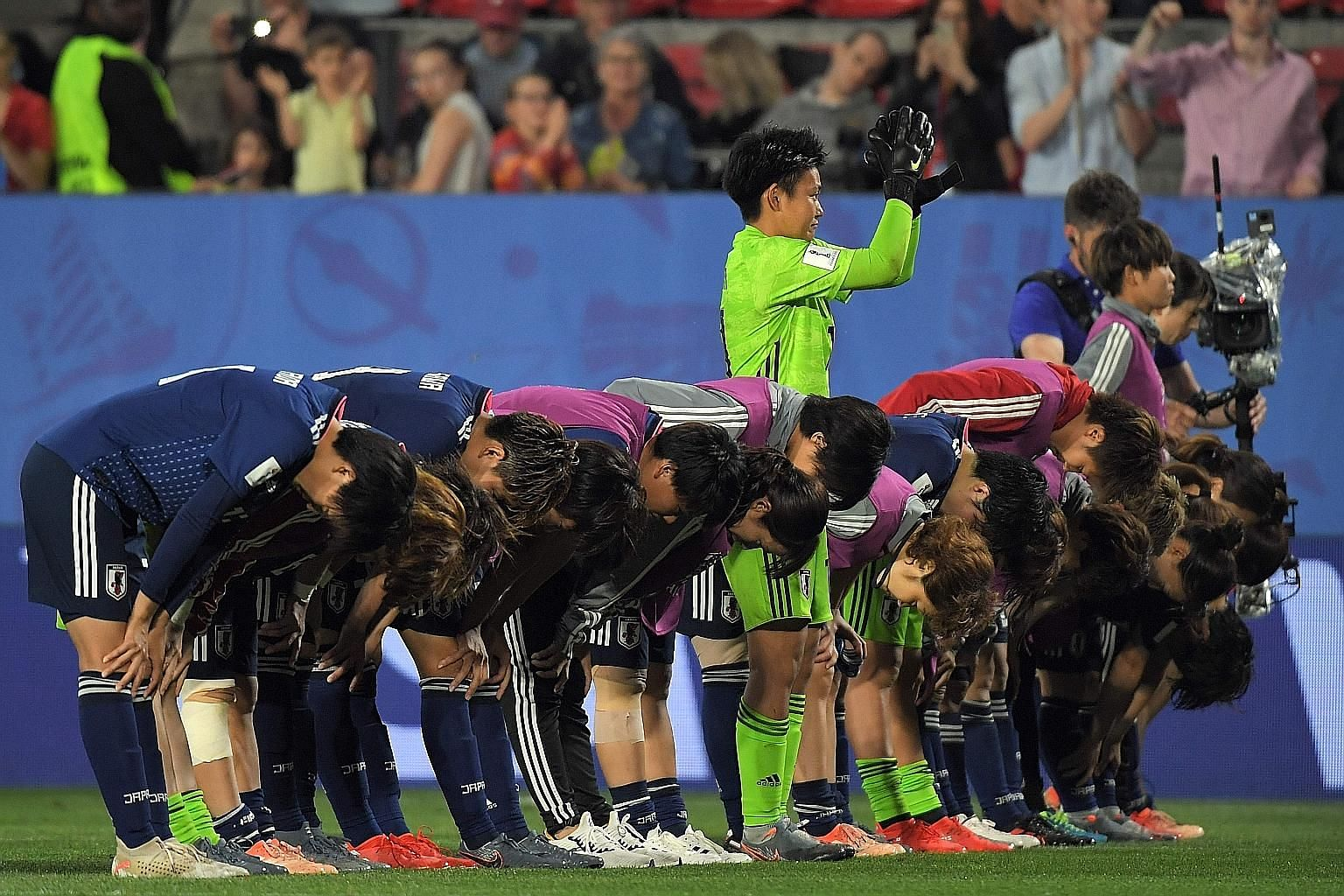 Japan's players bow in acknowledging their supporters after their 2-1 loss to the Netherlands in the round of 16. The Japanese, World Cup finalists in 2015, fell to a late penalty. Below: Wang Shuang failed to shine for China in their 2-0 defeat by I