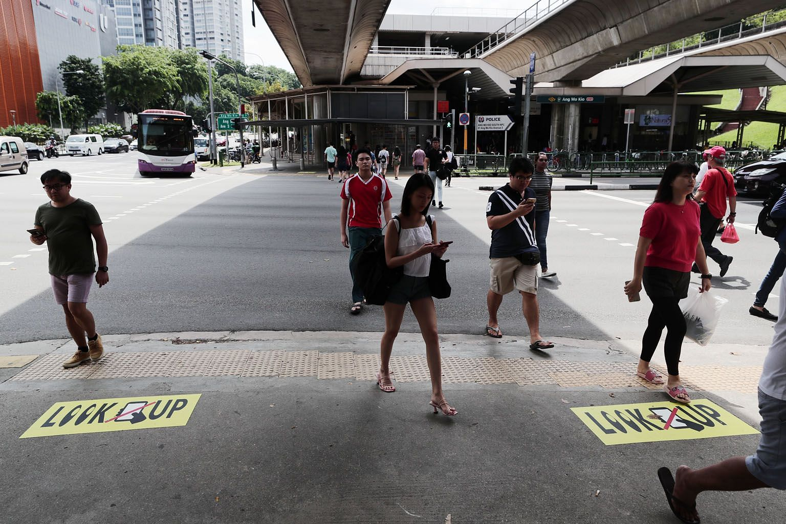 Despite stickers and small billboards reminding pedestrians not to be distracted while crossing the road near Ang Mo Kio MRT station, many were seen glued to their devices yesterday. ST PHOTO: KELVIN CHNG