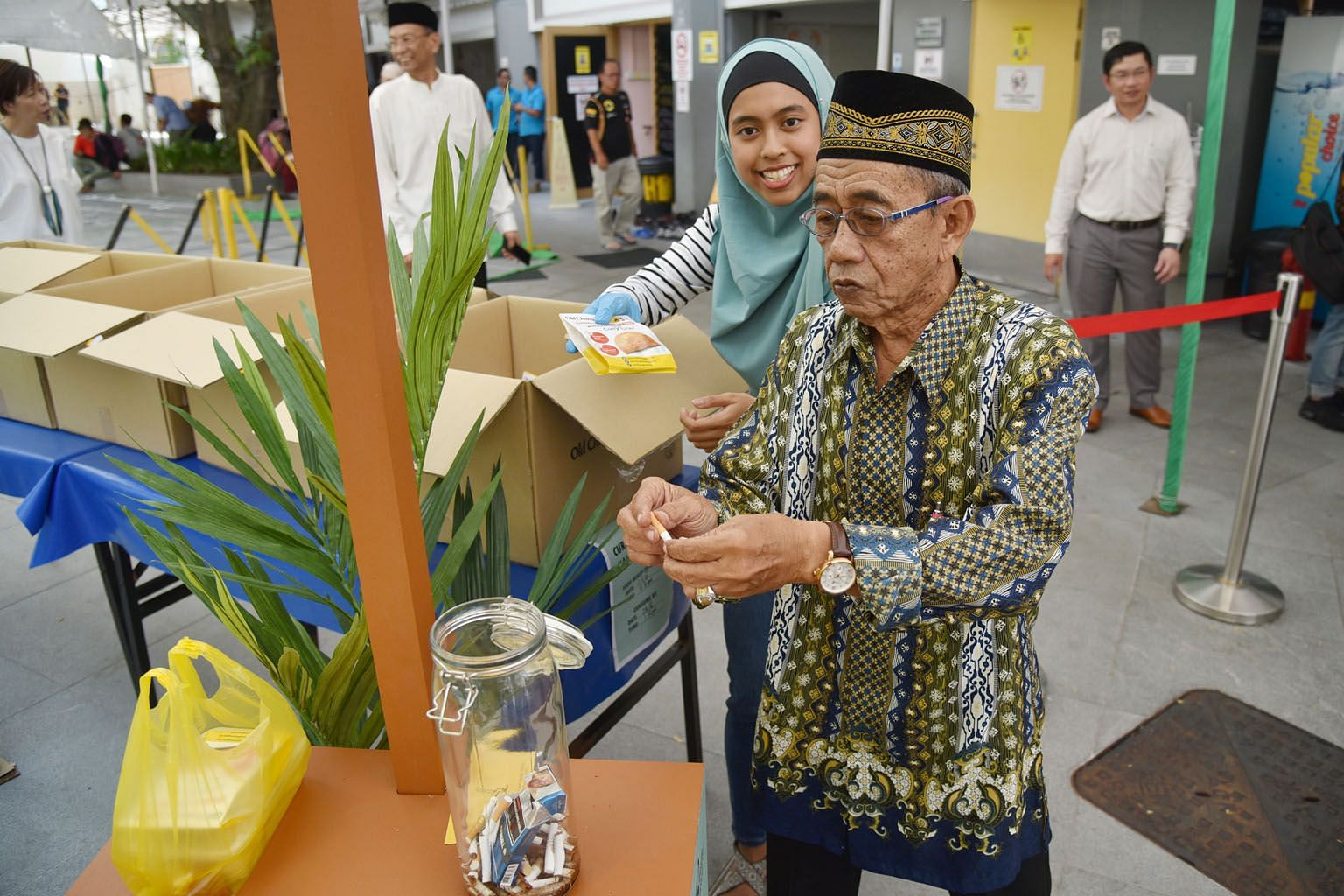 Mr Wahab Mohamed, 77, giving up his cigarette in exchange for a curry puff at Sultan Mosque yesterday. Until mid-October, smokers who visit Puff For A Puff booths at 22 partner mosques can trade cigarettes for free curry puffs, before choosing to joi