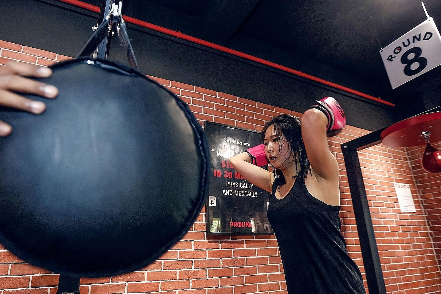 Journalist Clara Lock working a horizontal punching bag at kickboxing circuit training gym 9Round, where members can join a workout - which comprises nine stations - anytime during opening hours.