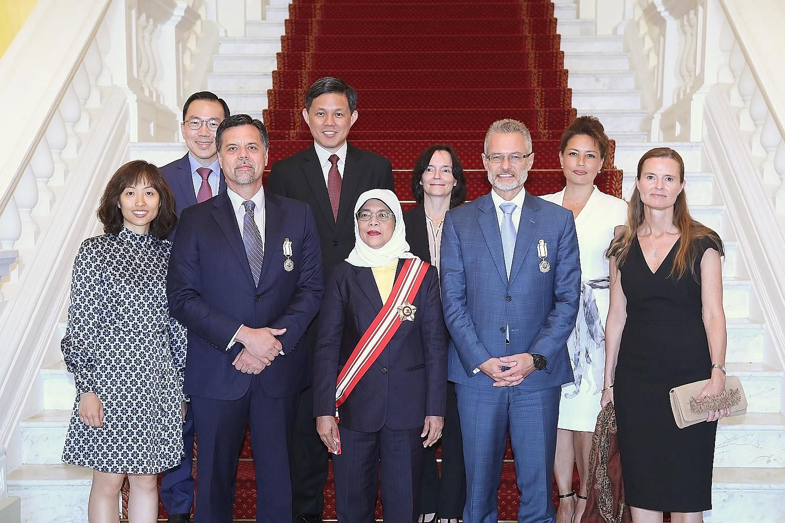 President Halimah Yacob at the investiture of The Public Service Medal last Thursday, flanked by (front row, second from left) Mr Wayne Russell Allan, ASML executive vice-president and Mr Oliver Tonby, senior partner and Asia chairman of McKinsey and