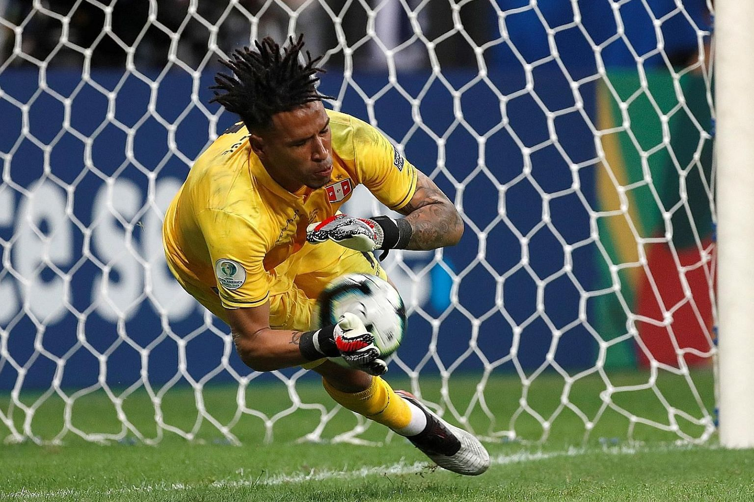 Left: Peru goalkeeper Pedro Gallese saving Uruguay's first penalty when Luis Suarez shoots straight into him at Arena Fonte Nova Stadium in Salvador, Brazil, on Saturday. Above: A distraught Suarez is comforted by Uruguay goalkeeper Fernando Muslera.