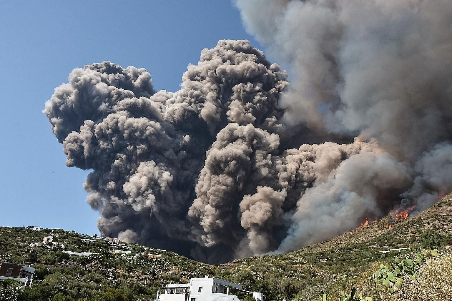 Smoke billowing across the hillside after the Stromboli volcano in Italy erupted on Wednesday, killing a hiker and sending tourists fleeing from the small island. Emergency workers yesterday brushed and scooped volcanic cinders from streets and the t