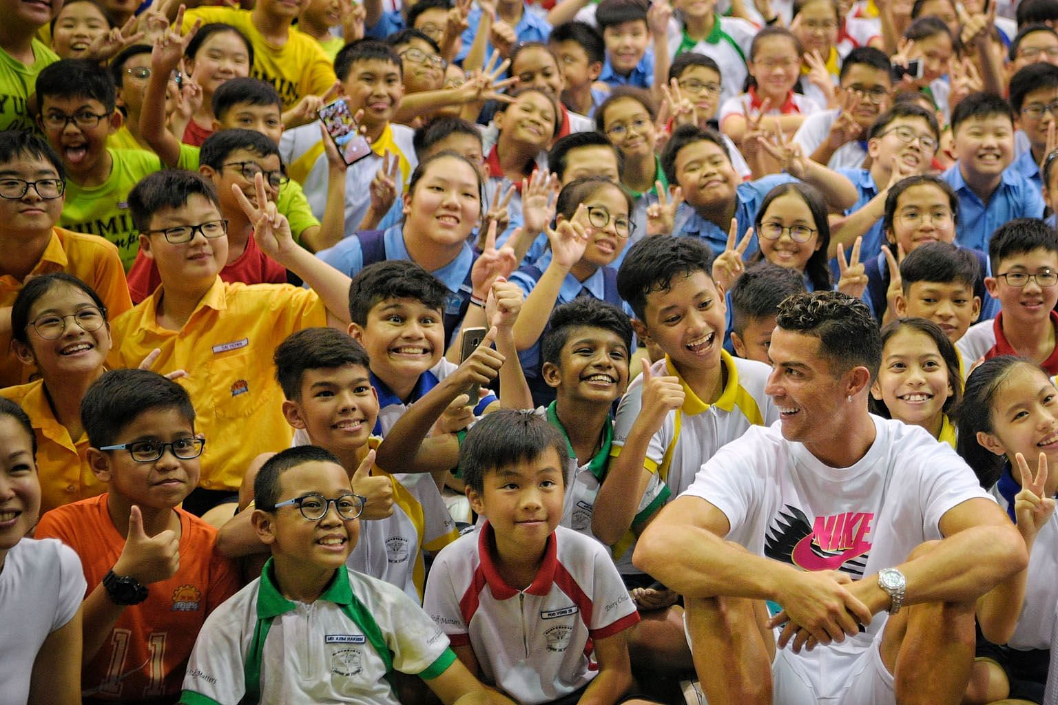 From above: The star-struck pupils from Yumin and Chongzheng primary schools giving Cristiano Ronaldo their seal of approval after his visit to Yumin's school hall in support of the Singapore Olympic Foundation-Peter Lim Scholarship. A drawing of Ron