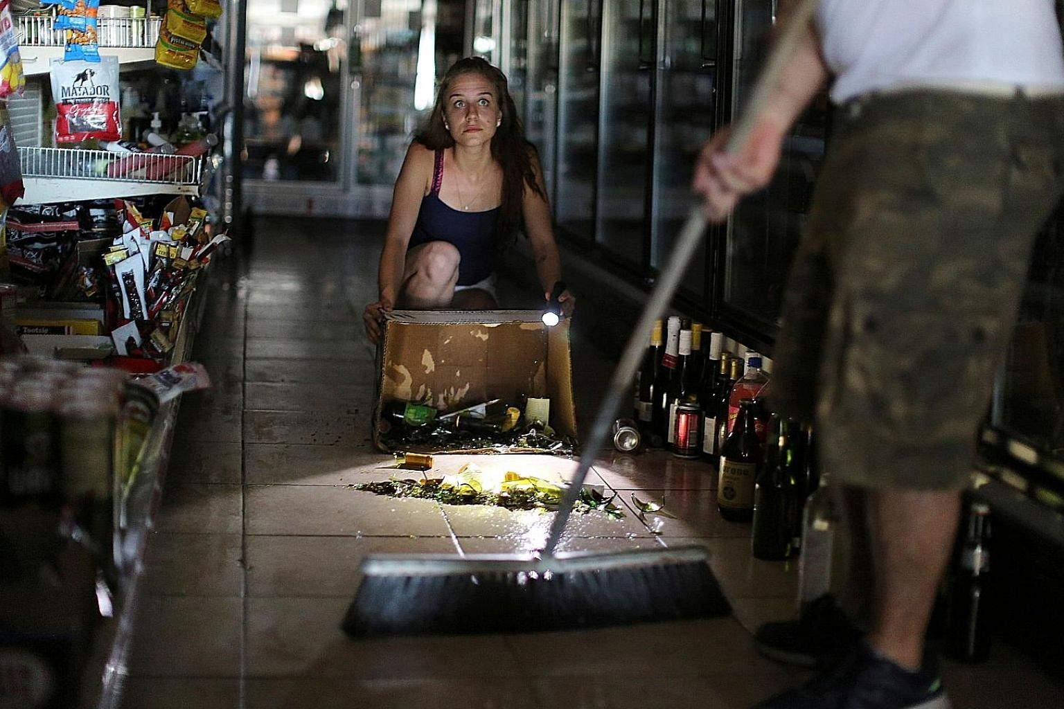 Owners of a liquor store cleaning up after a 6.4-magnitude earthquake struck Southern California on Thursday. PHOTO: REUTERS