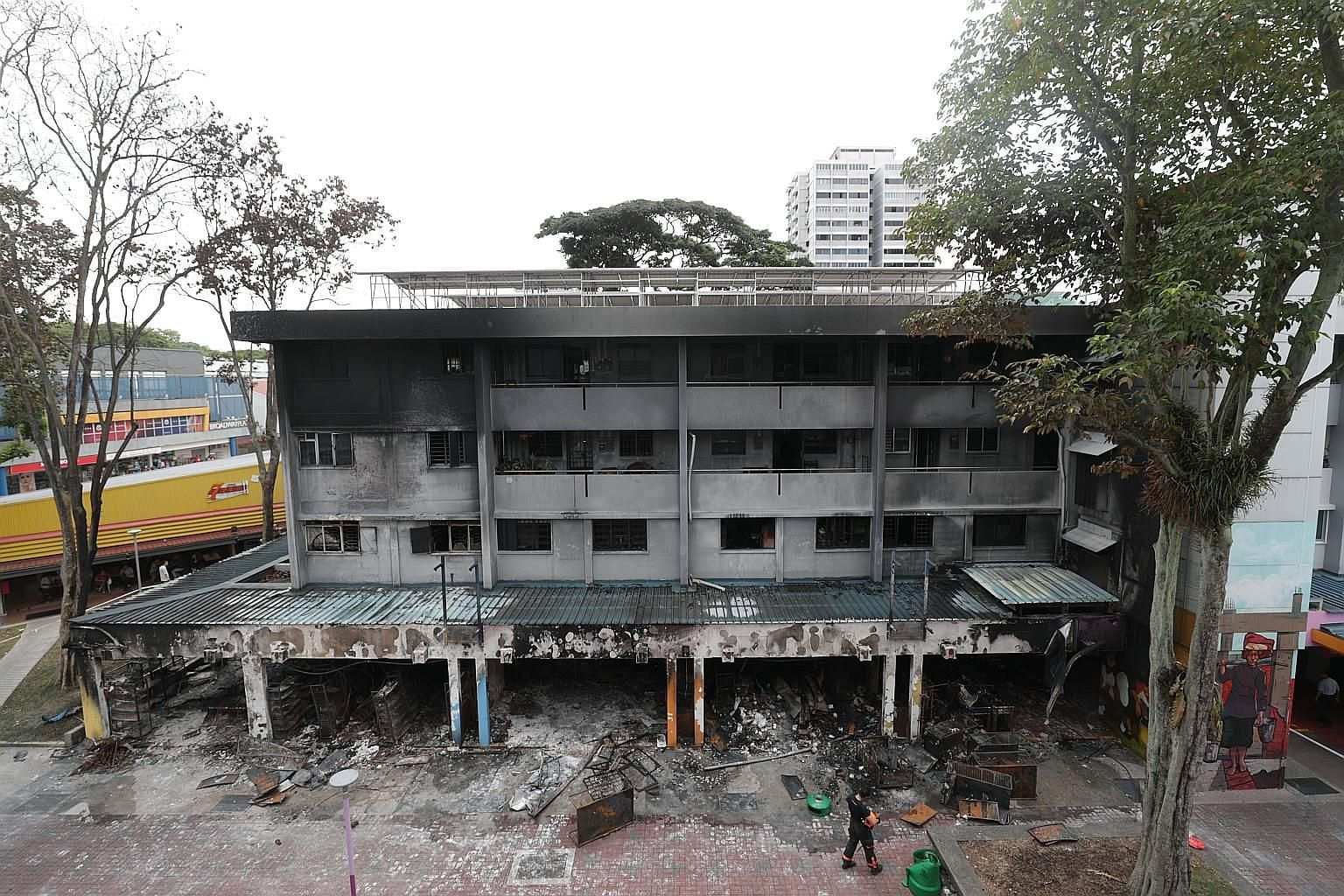 The gutted remains of the shops on the first level of Block 720 (above) and the facade of the four-storey block. The cause of the fire, which involved a paint shop and three other units, is still under investigation. Occupants from 16 shops and 28 re
