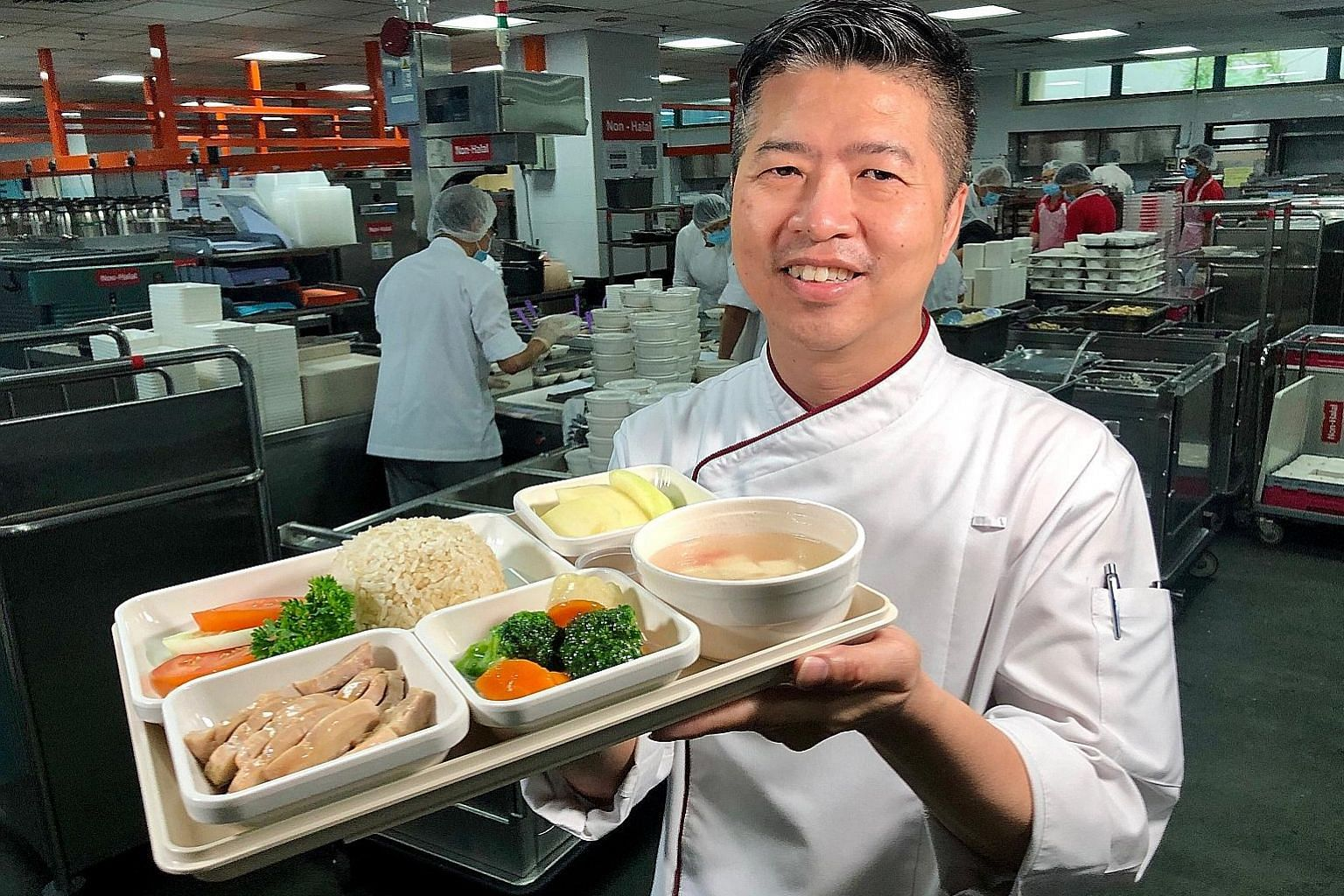 Tan Tock Seng Hospital's senior production chef Leo Yuin Thim with Poached Hainanese Chicken served with mixed brown rice.