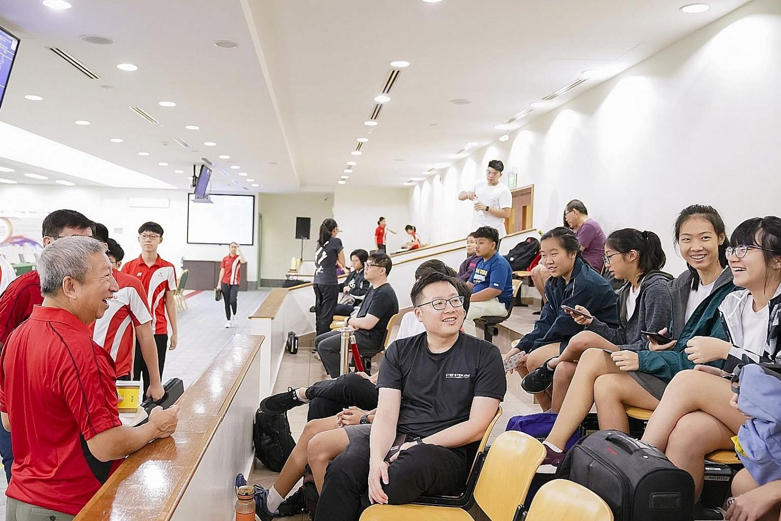 Ng Ser Miang (left), chairman of the Singapore Olympic Foundation, chatting with some shooters at the opening ceremony of the Singapore Youth Olympic Festival at the Safra Indoor Air Weapon Range in Safra Yishun yesterday morning. Ng was the guest of
