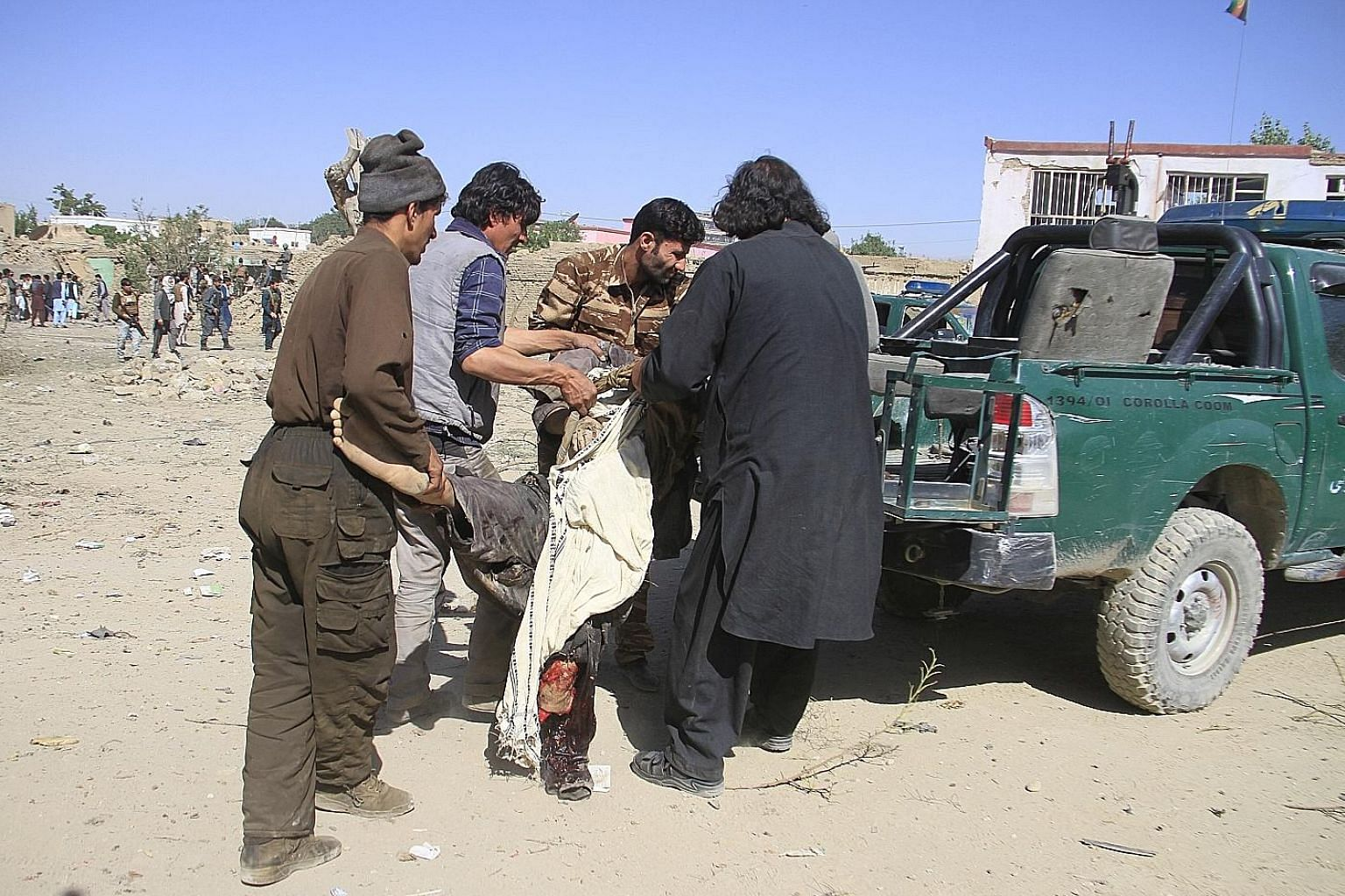 Afghans moving an injured man from the scene after Taleban fighters detonated a car bomb in Ghazni. The Taleban have continued attacks despite increased US efforts towards a peace deal to end the 18-year war.